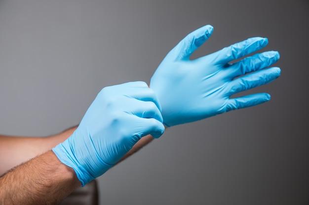 Mężczyzna zakłada gumowe rękawiczki na szarej ścianie