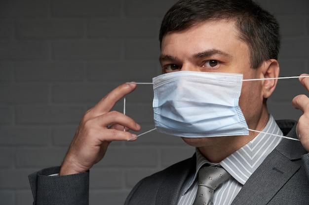 Mężczyzna zakłada maskę na twarz w celu ochrony indywidualnej antywirusowej