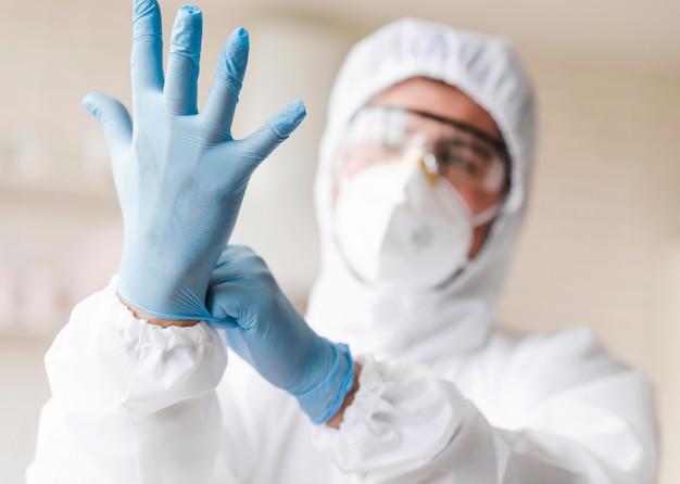 Mężczyzna zakłada niebieskie rękawiczki