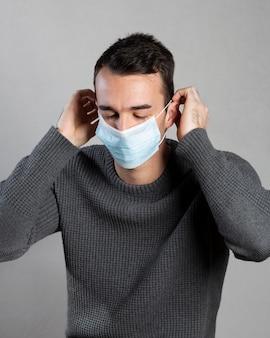 Mężczyzna zakładający maskę medyczną dla ochrony