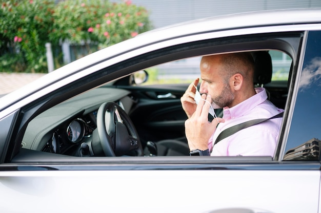 Mężczyzna zakładający maskę ochronną w samochodzie