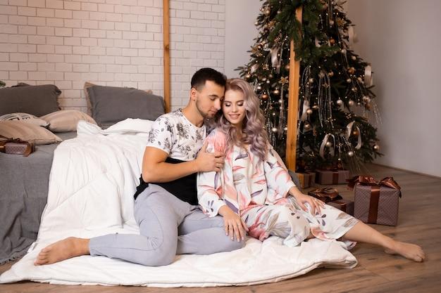 Mężczyzna zakochana kobieta siedzi na podłodze w pobliżu łóżka w domu na choince na tle
