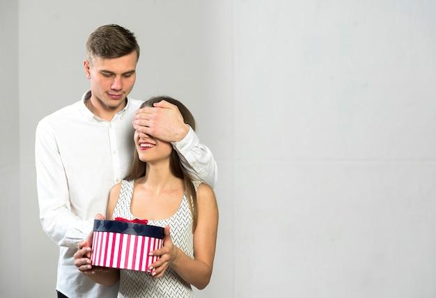 Mężczyzna zakrywa oczy kobieta z prezenta pudełkiem
