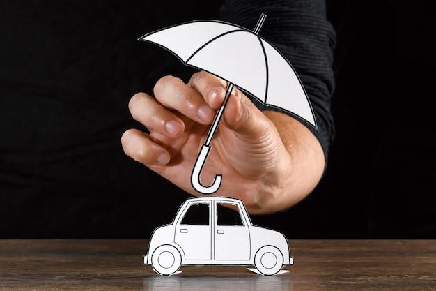 Mężczyzna zakrywa papierowy samochód z papierowym parasolem
