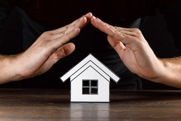 Mężczyzna zakrywa rękami papierowy dom