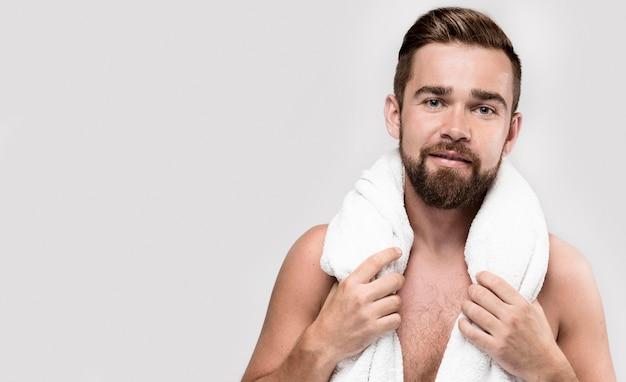 Mężczyzna zakrywa się białym ręcznikiem z miejsca na kopię