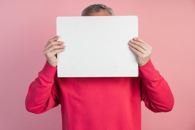 Mężczyzna zakrywa twarz białą kartką papieru