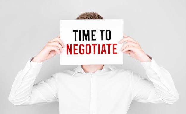 Mężczyzna zakrywa twarz białą kartką z tekstem czas do negocjacji