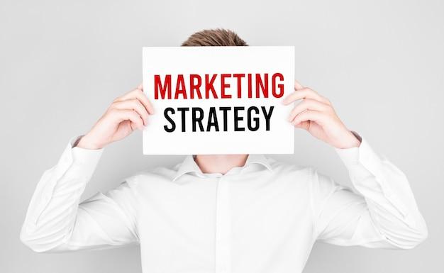 Mężczyzna zakrywa twarz białą księgą z tekstem strategia marketingowa