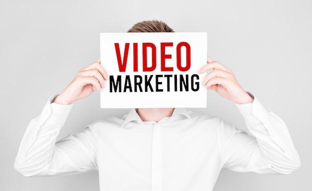 Mężczyzna zakrywa twarz białą księgą z tekstem video marketing