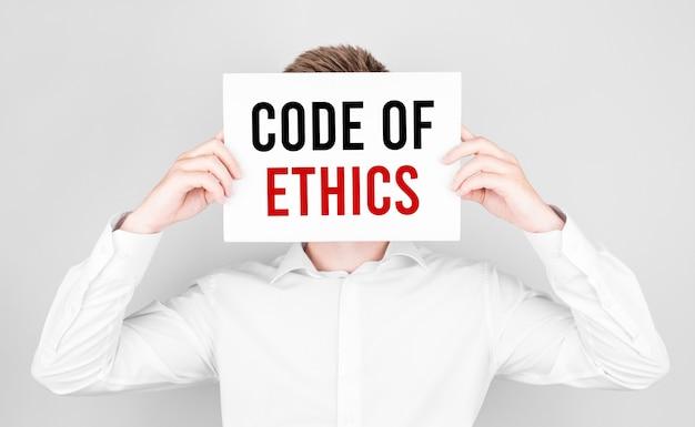 Mężczyzna zakrywa twarz białym papierem z tekstem kodeks etyki