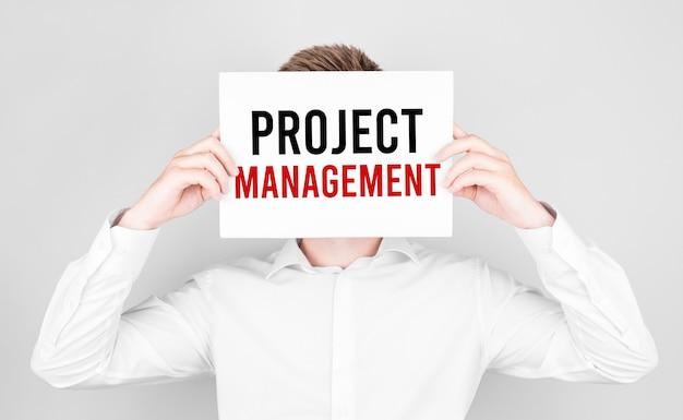 Mężczyzna zakrywa twarz białym papierem z tekstem zarządzanie projektami