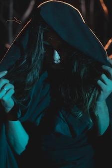 Mężczyzna zakrywa twarz kapturem w nocy