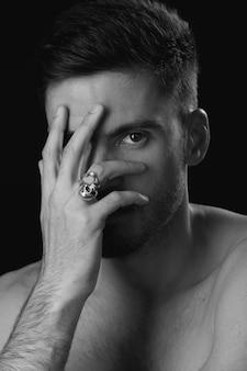 Mężczyzna zakrywa twarz ręką patrząc w kamerę