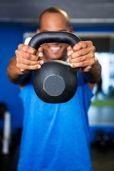 Mężczyzna zakrywa twarz z kettlebell w gym