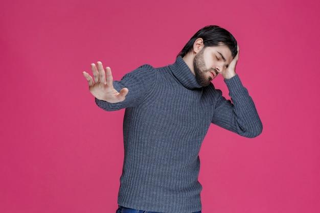 Mężczyzna zakrywa uszy rękami ze względu na głośność.
