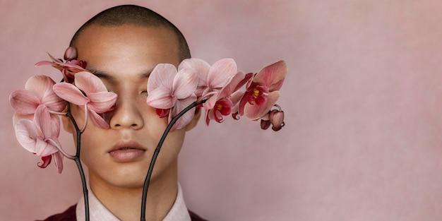 Mężczyzna zakrywający oczy kwiatami