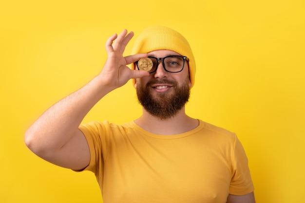 Mężczyzna zakrywający oko bitcoinem na żółtym tle