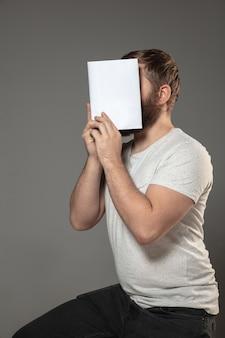 Mężczyzna zakrywający twarz książką podczas czytania na szarej ścianie