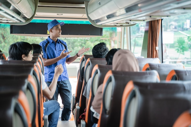 Mężczyzna załoga autobusu w mundurze i kapeluszu przedstawia pasażerom praktyczne gesty przed wyjazdem na wycieczkę autobusową