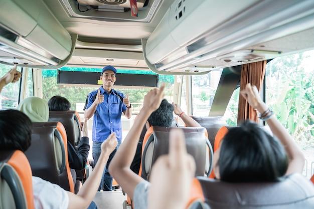 Mężczyzna załoga autobusu w niebieskim mundurze i kapeluszu z kciukami do góry podczas sprawdzania gotowości pasażerów przed wyjazdem na wycieczkę autobusową