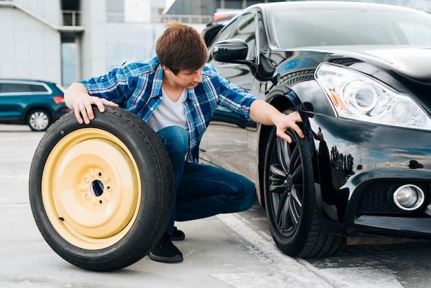 Mężczyzna zamienia oponę samochodową na zapasową