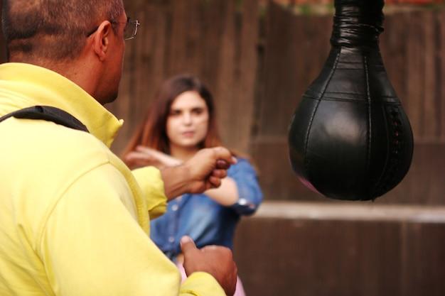 Mężczyzna zamierzający uderzyć kobietę. mąż wymachuje pięściami w żonę. worek treningowy.