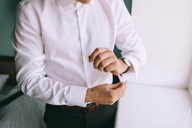 Mężczyzna zamyka jego spinki do mankietów z bliska. biznesmen lub narzeczony przygotowuje się do wyjścia.