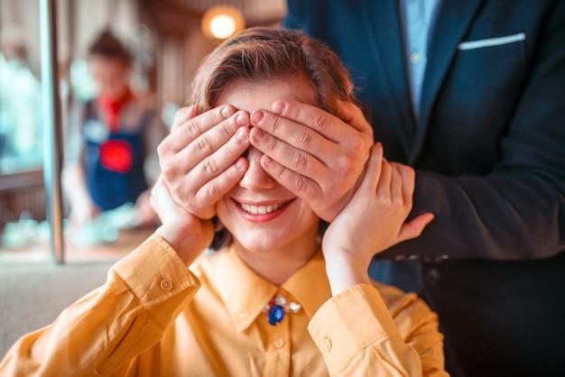 Mężczyzna zamyka oczy ręce do pięknej kobiety w restauracji.