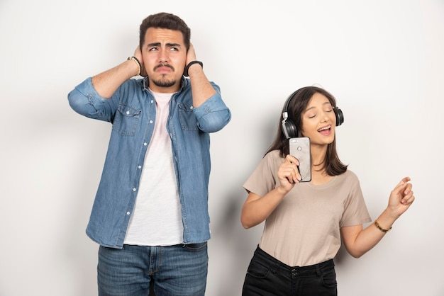 Mężczyzna zamyka uszy, podczas gdy kobieta śpiewa swoje serce.