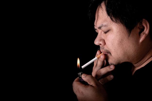 Mężczyzna zapala papierosa zapalniczką