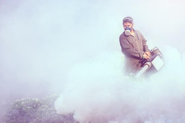 Mężczyzna zaparowuje, aby wyeliminować komara, aby zapobiec rozprzestrzenianiu się gorączki denga i wirusa zika