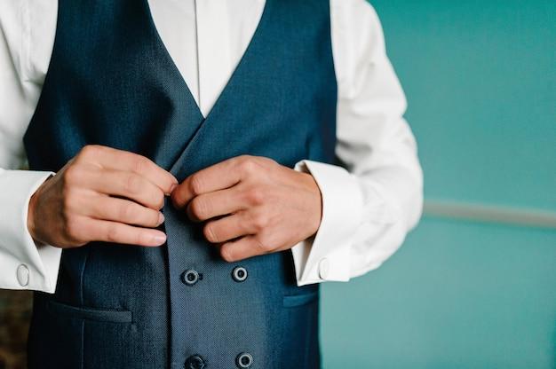 Mężczyzna zapina kamizelkę. zbliżenie. perfekcyjne w każdym szczególe. nowoczesny biznesmen. moda strzał przystojny młody człowiek w eleganckim klasycznym garniturze. uroda męska, moda.