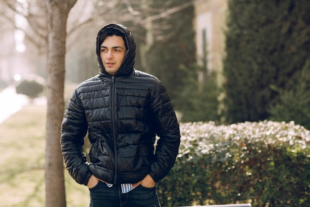 Mężczyzna zapinający do końca czarną skórzaną kurtkę i noszący bluzę z kapturem, aby zapobiec przeziębieniu. zdjęcie wysokiej jakości