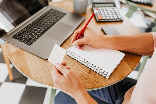 Mężczyzna zapisuje informacje biznesowe w notesie w miejscu pracy w biurze z cutaway i laptopa