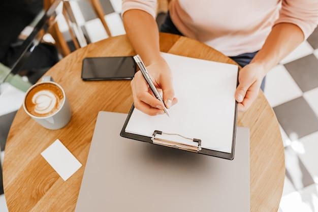 Mężczyzna zapisuje informacje biznesowe w notesie w miejscu pracy w biurze z laptopem