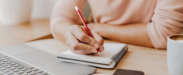 Mężczyzna zapisuje informacje biznesowe w notesie w miejscu pracy w biurze