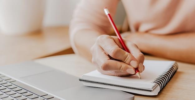 Mężczyzna Zapisuje Informacje Biznesowe W Notesie W Miejscu Pracy W Biurze Premium Zdjęcia