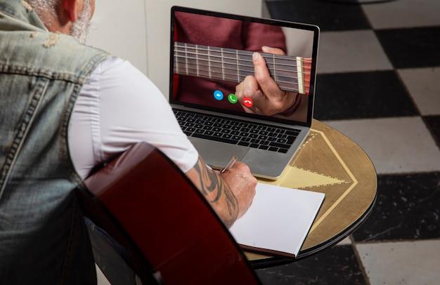 Mężczyzna zapisuje notatki w notesie podczas zajęć online na laptopie. szkolenia online, zajęcia online.