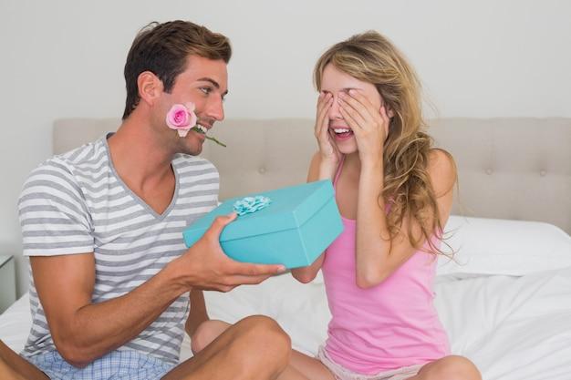 Mężczyzna zaskakująca kobieta z prezenta pudełkiem w łóżku