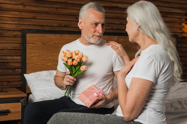 Mężczyzna zaskakująca żona z kwiatami i prezentem