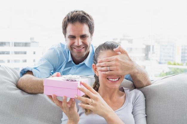 Mężczyzna zaskakuje swoją dziewczyną z różowym prezentem na kanapie