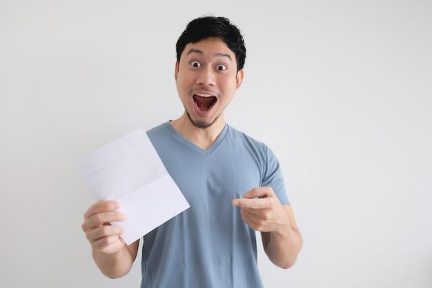 Mężczyzna Zaskoczony I Zszokowany Listem W Jego Dłoni Na Białym Tle. Premium Zdjęcia