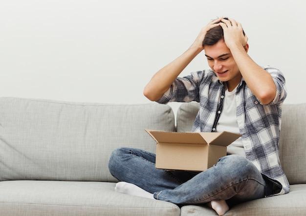 Mężczyzna zaskoczony pudełkiem dostawy