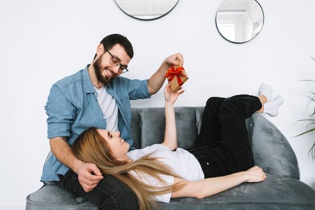 Mężczyzna zaskoczył swoją dziewczynę prezentem, szczęśliwą parą świętującą walentynki lub rocznicę