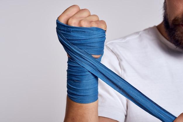 Mężczyzna zawiązuje rękę bandażami bokserskimi