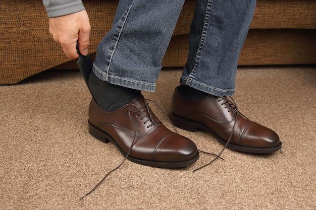 Mężczyzna zawiązuje sznurówki na klasycznych brązowych butach