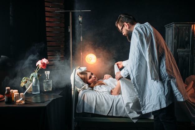 Mężczyzna zawija koc ukochaną kobietę w szpitalnym łóżku