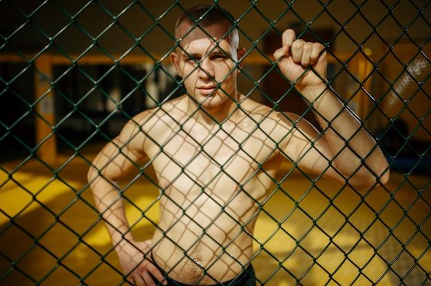 Mężczyzna zawodnik mma stojący przy siatce w klatce na siłowni.
