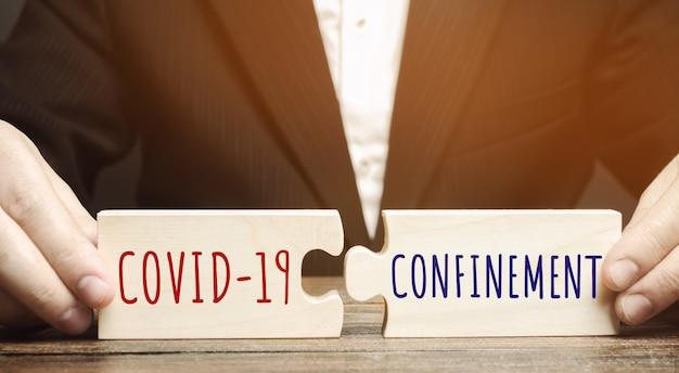 Mężczyzna zbiera drewniane łamigłówki ze słowami covid-19 i zakażenie pandemią coronavirus